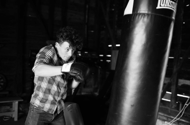 A teen hits a punching bag in this lifestyle shoot captured by professional Helen Bartlett.