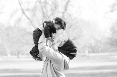 London's parks and green spaces are an idea place to have a family shoot while visiting London and the UK. This mother holds up her son while playing in a London park.