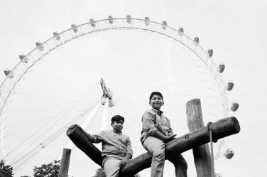 Two brothers play in front of the London Eye - the capital's answer to a big wheel or ferris