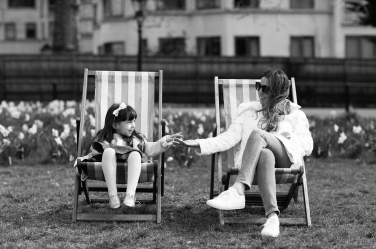 A mother and daughter sit in Hyde Park's iconic striped deckchairs during their London holiday. They made time to hire a portrait photographer to take these photos, so they have memories of their stay when they return home.