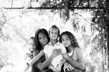 A black and white family portrait of a mother and three children, taken during a London portrait shoot on their visit to the capital.
