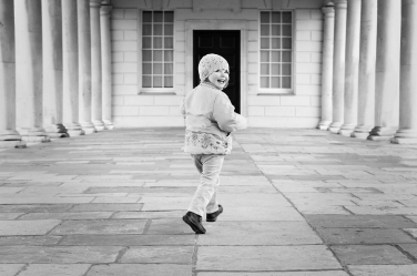 The majestic columns of Greenwich are the background for a portrait of this smiling little girl. Her photo was taken as part of a London holiday portrait shoot by London photographer Helen Bartlett.