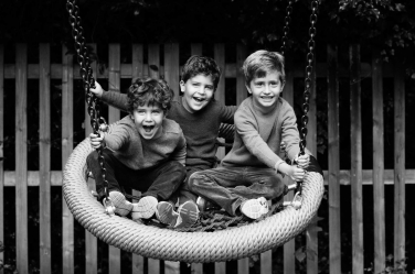 London vacation photographer Helen Bartlett captures this precious moment between three brothers on a swing in the UK capital.