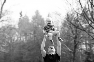 A father lifts his son into the air during a London vacation portrait session. They booked the session ahead of their London vacation.