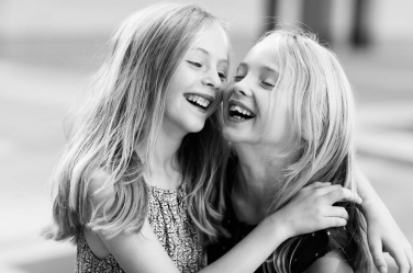 Sisters laugh their way through their London holiday portraits, wobbly tooth and all.