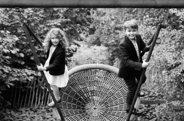 A brother and sister rock a grown-up take on a park swing during their London portrait session. The portraits were taken while they were on holiday in London.