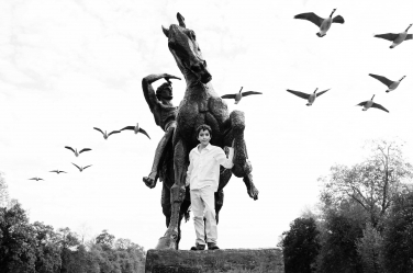 A flock of geese fly over a young man having his portrait taken during a London holiday.