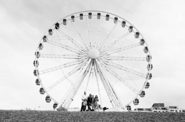 A family portrait in front of a ferris wheel during this family's UK visit. The photo was taken by professional photographer Helen Bartlett, who specialises in family shoots taken during holidays or vacations in the UK.
