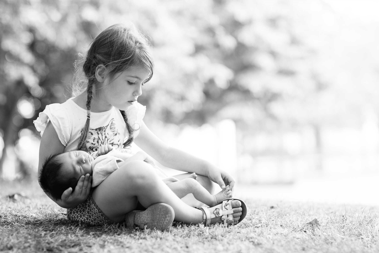 A big sister cradles her newborn sibling in this outdoor black and white portrait. This is an example of newborn and family photography in Bethnal Green .