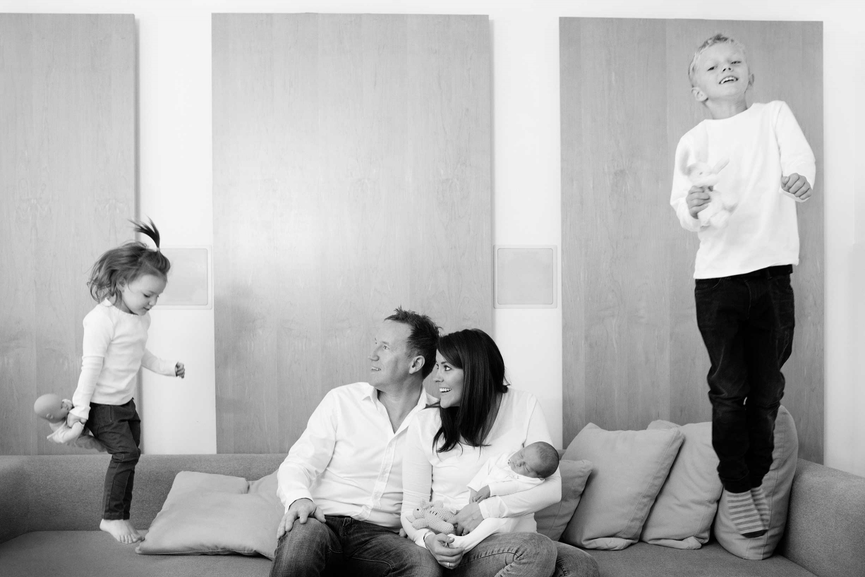 Parents hold their newborn while their older two children leap around on the sofa.