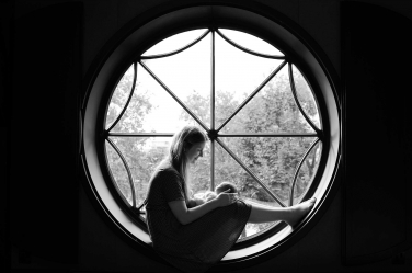 A mother holds her brand new infant in a decorative, circular window for a timeless classic London newborn portrait.