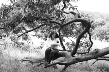 A mother cradles her newborn child in the crook of her arm. A tree branch naturally curls around both of them in a protective way.