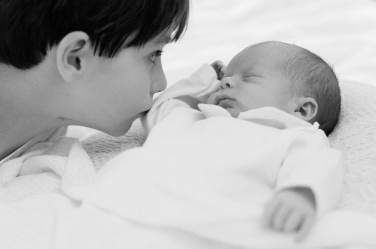 A toddler kisses his tiny, sleeping newborn brother in this touching newborn family portrait by London photographer Helen Bartlett.