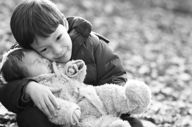 A big brother snuggles his newborn sibling outdoor in the autumn leaves.