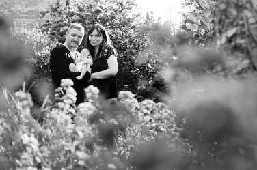 Newborn portraits can take place outdoors in London during spring and summer, allowing a natural setting to surround the new family.