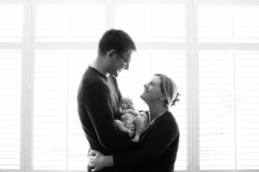 A newborn nestles between its parents in this stylish newborn portrait taken by London newborn photographer Helen Bartlett. Helen works in black and white only for timeless newborn photos.