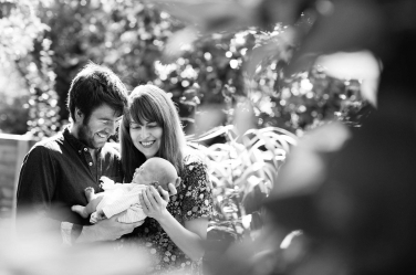 A newborn boy wrapped up in sunshine and parental joy in the great outdoors. Not all newborn portraits have to be taken indoors - a garden or park are a great alternative in London's warmer months.