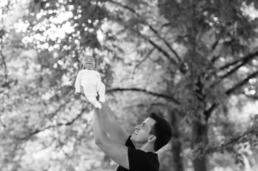 A father holds up his newborn child proudly, with a natural background of leaves.