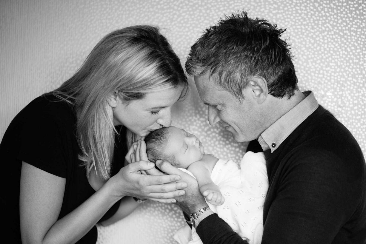 Mum and Dad cradle their newborn child in this sensitive newborn portrait in black and white.