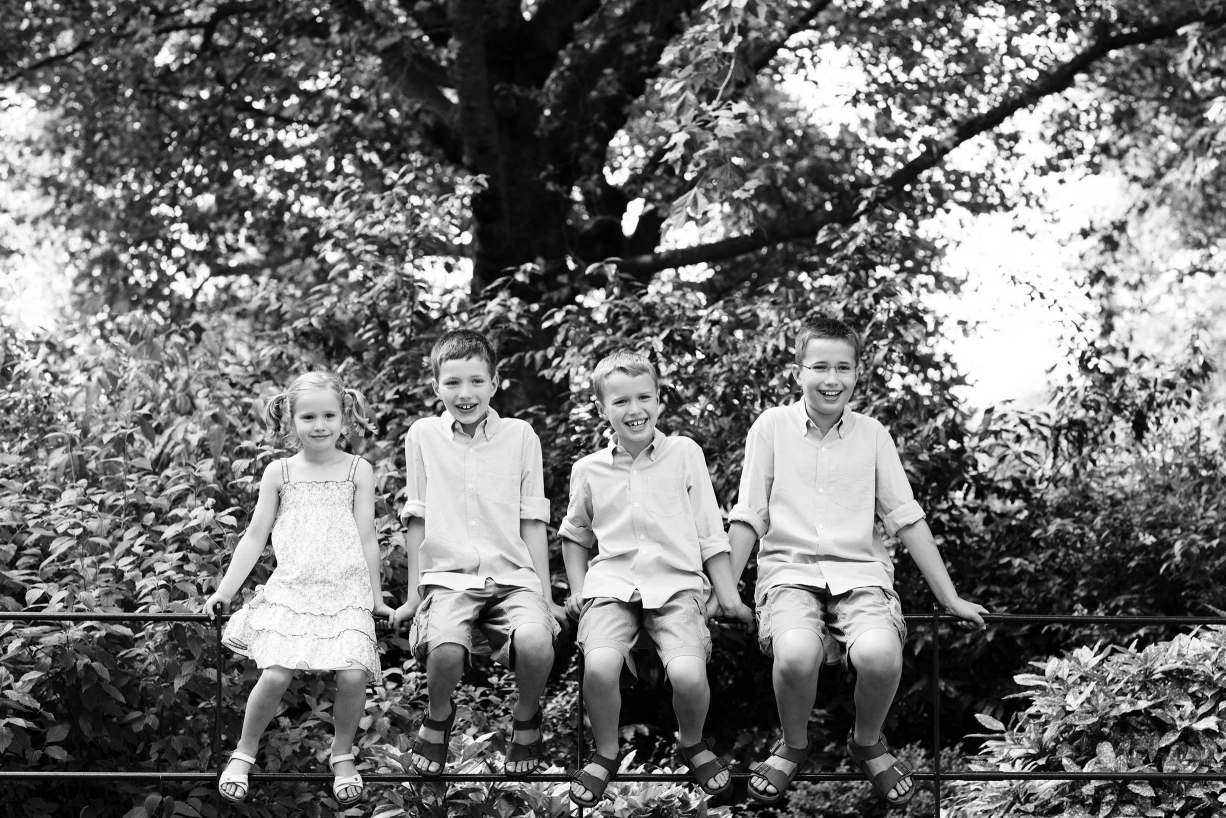 Four children are photographed in front of a tree in this example of Battersea family photography
