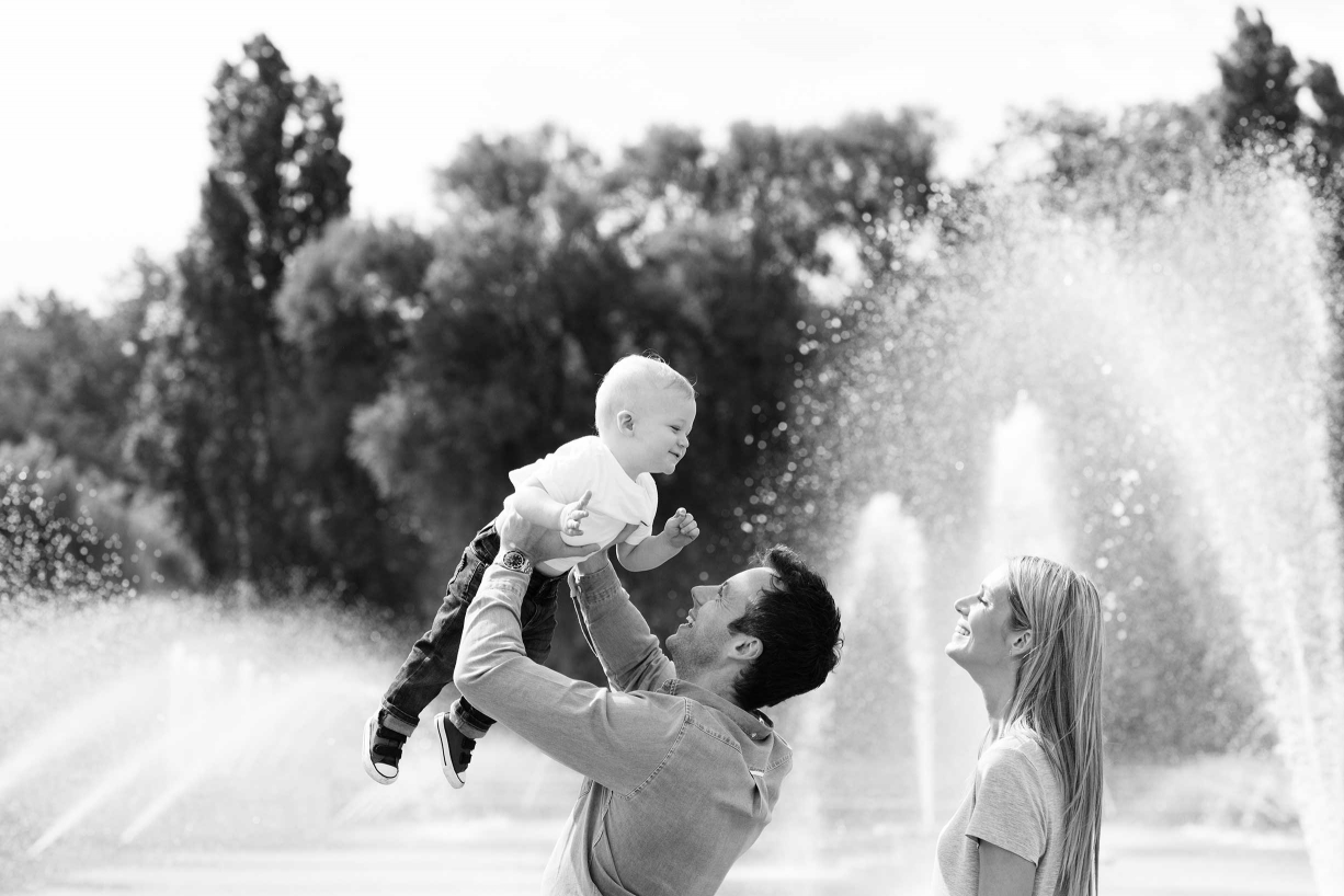 Battersea family photography - a family holds their child aloft in front of fountains.