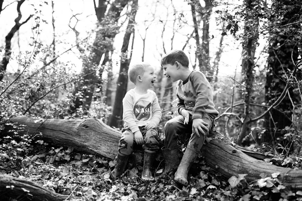 A fallen log provides just the spot for a sibling chat during a Blackheath family photo shoot.