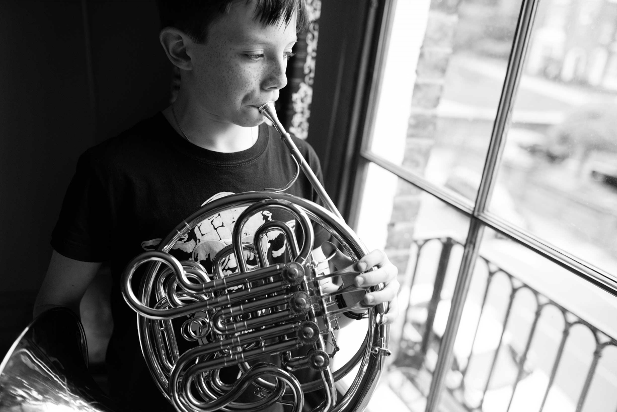A child plays their French horn during a Blackheath portrait session by professional photographer Helen Bartlett.