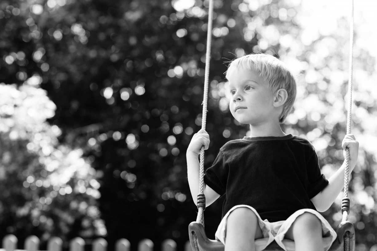 Chiswick family photographer Helen Bartlett captures this moment of a young girl on a swing in contemplation.