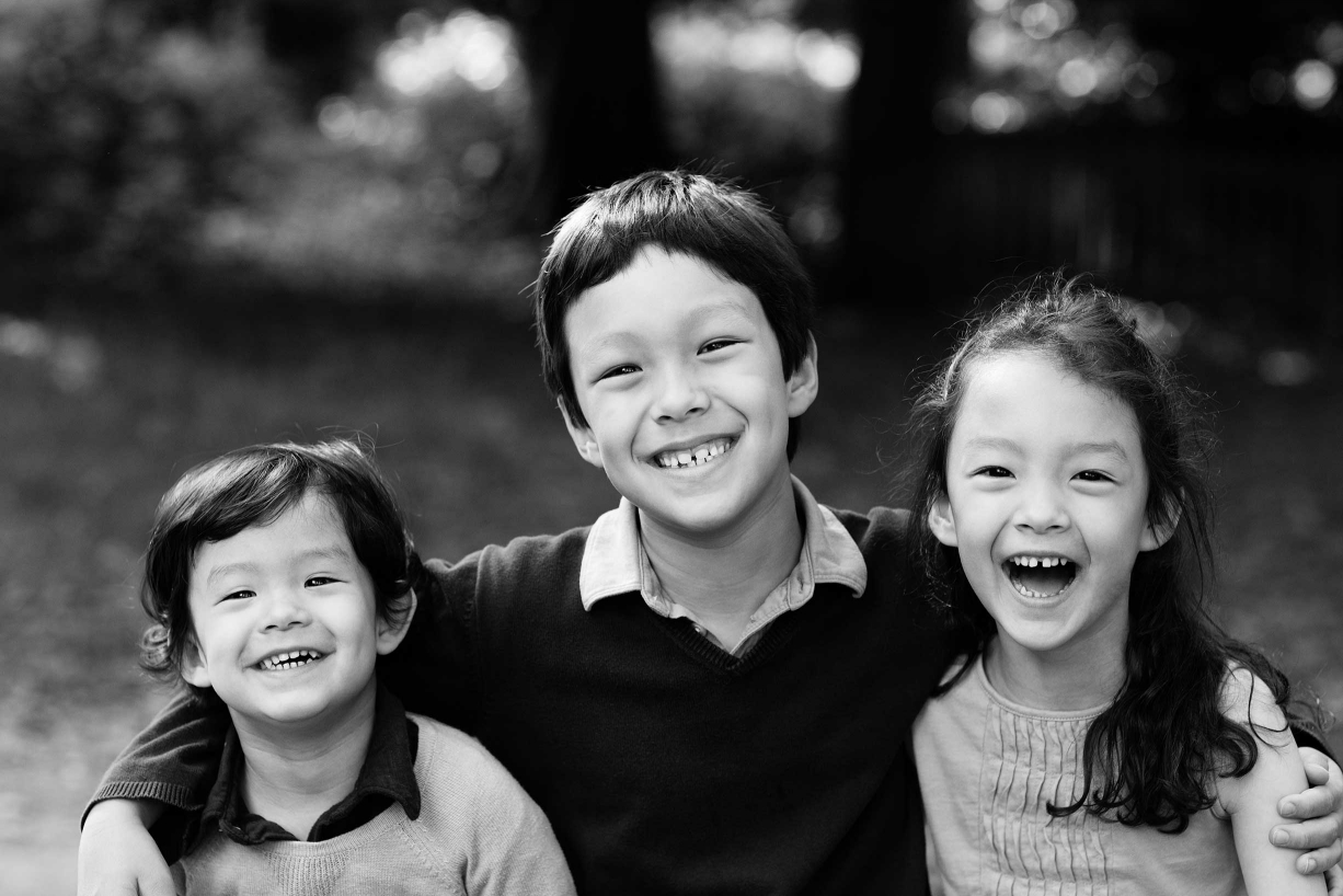 Siblings giggle during their family photography in Knightsbridge