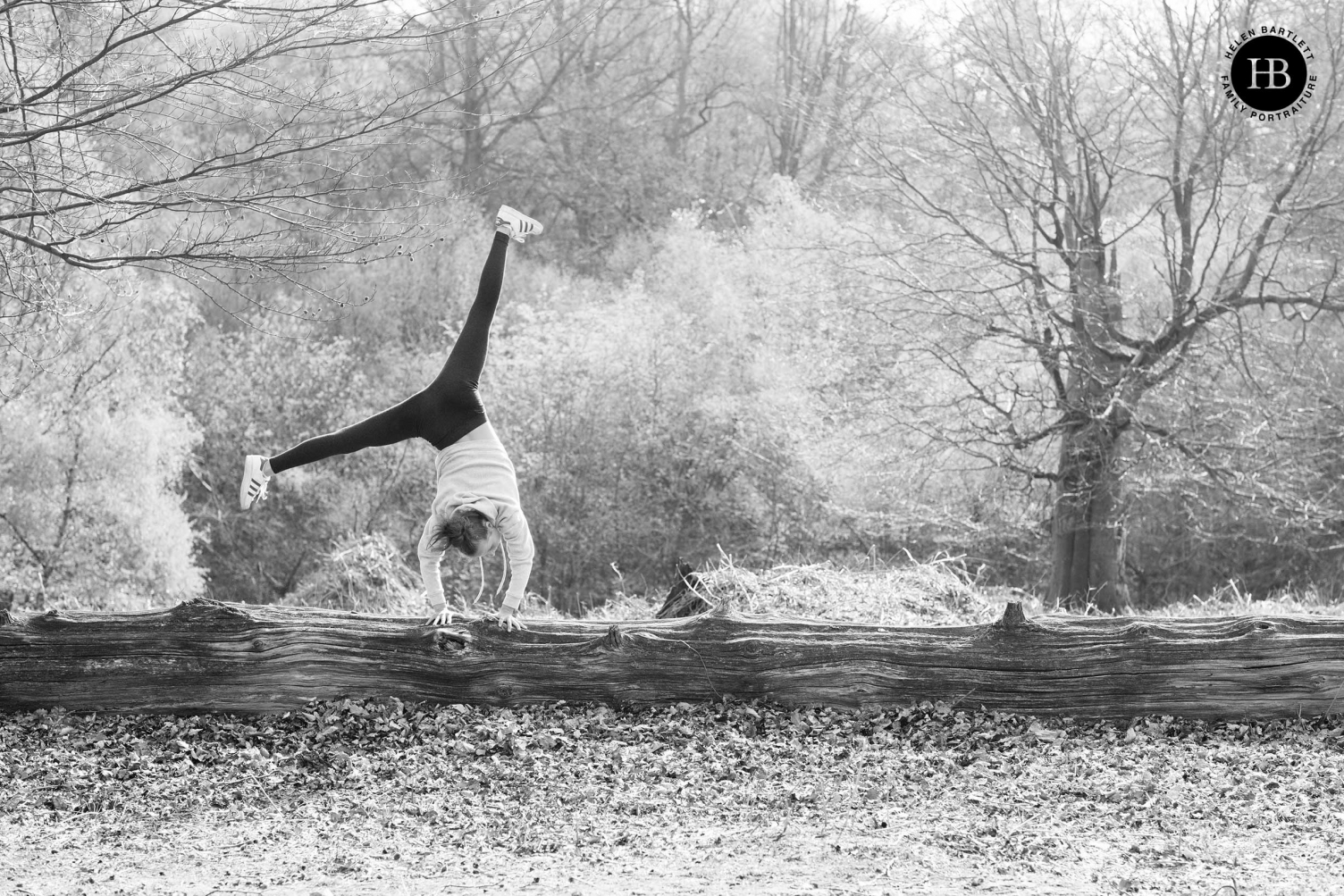 A girl cartwheels across a garden in this black and white photo taken during a family photoshoot.