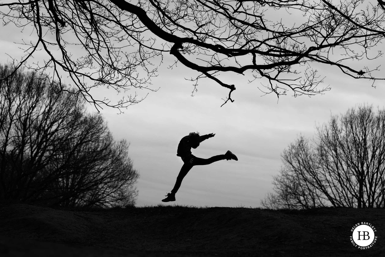 A girl dances on the horizon, framed by tree silhouettes in this evocative black and white photo taken during a portrait session in London.