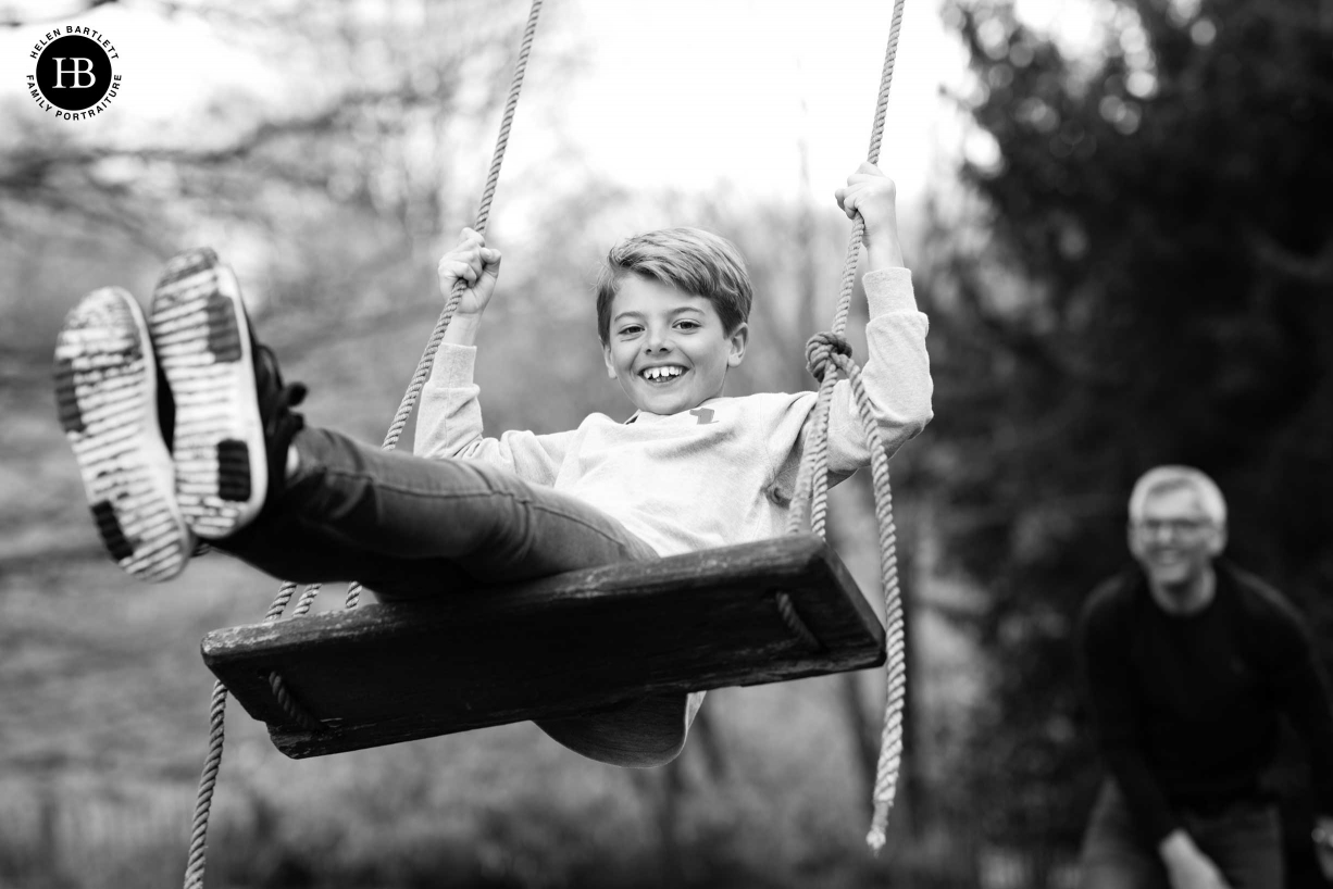 Black and white family photography of a boy on a swing.