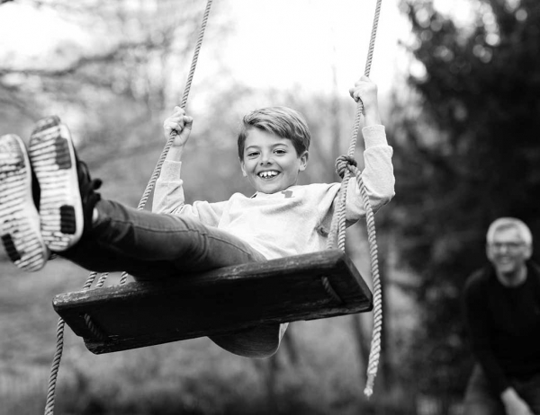Family photoshooot 'Just One' of a boy on a swing in black and white.