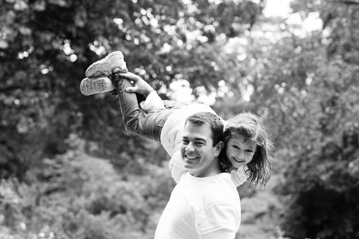 A dad lifts his daughter high into the air during their Hammersmith family photo session.
