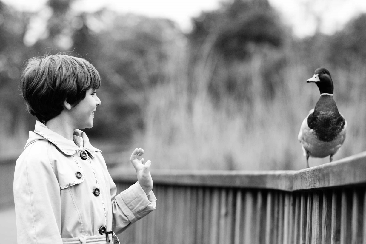 A girl and a friendly duck get to know each other during a family portrait session.