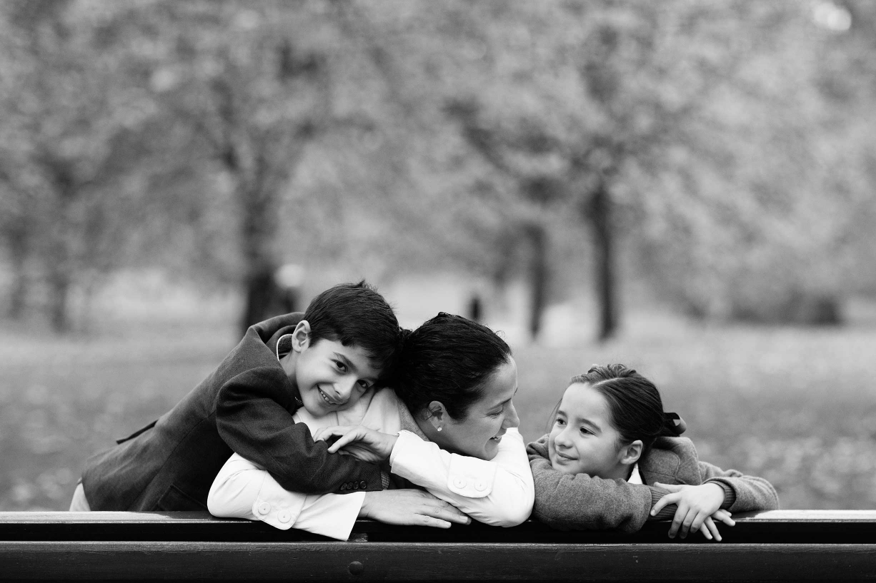 A family hugs on a park bench during their Hammersmith family portraits.