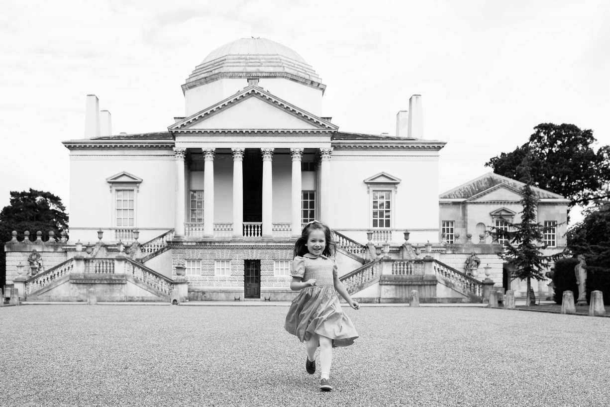 A girls runs towards the camera during their family photos.