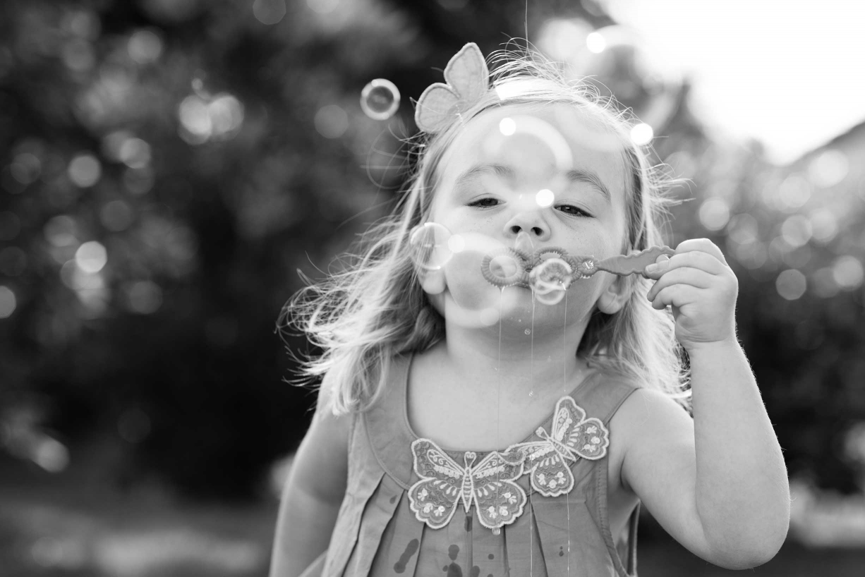 Family photography in Hampstead includes blowing bubbles and other fun activities.