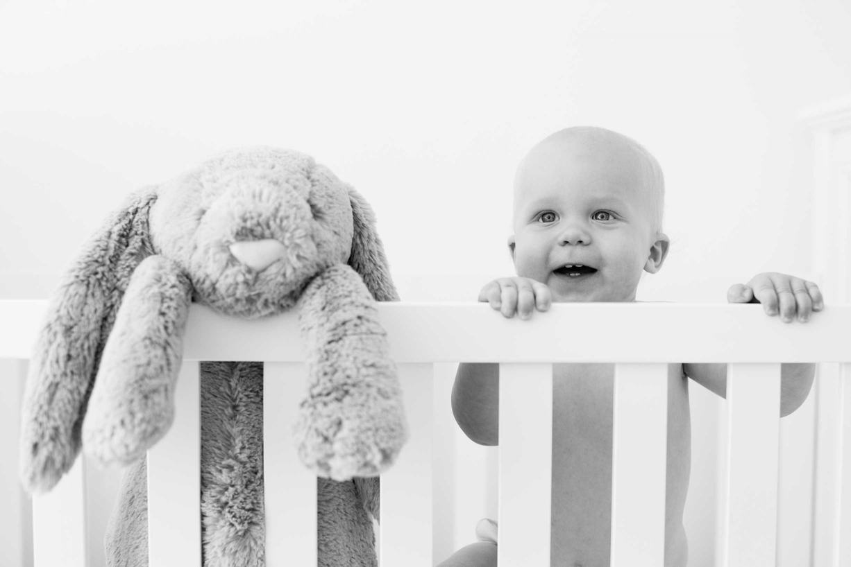 A baby and its toy rabbit peer over the edge of their cot during their professional family portrait shoot in the Royal Borough of Kensington and Chelsea.