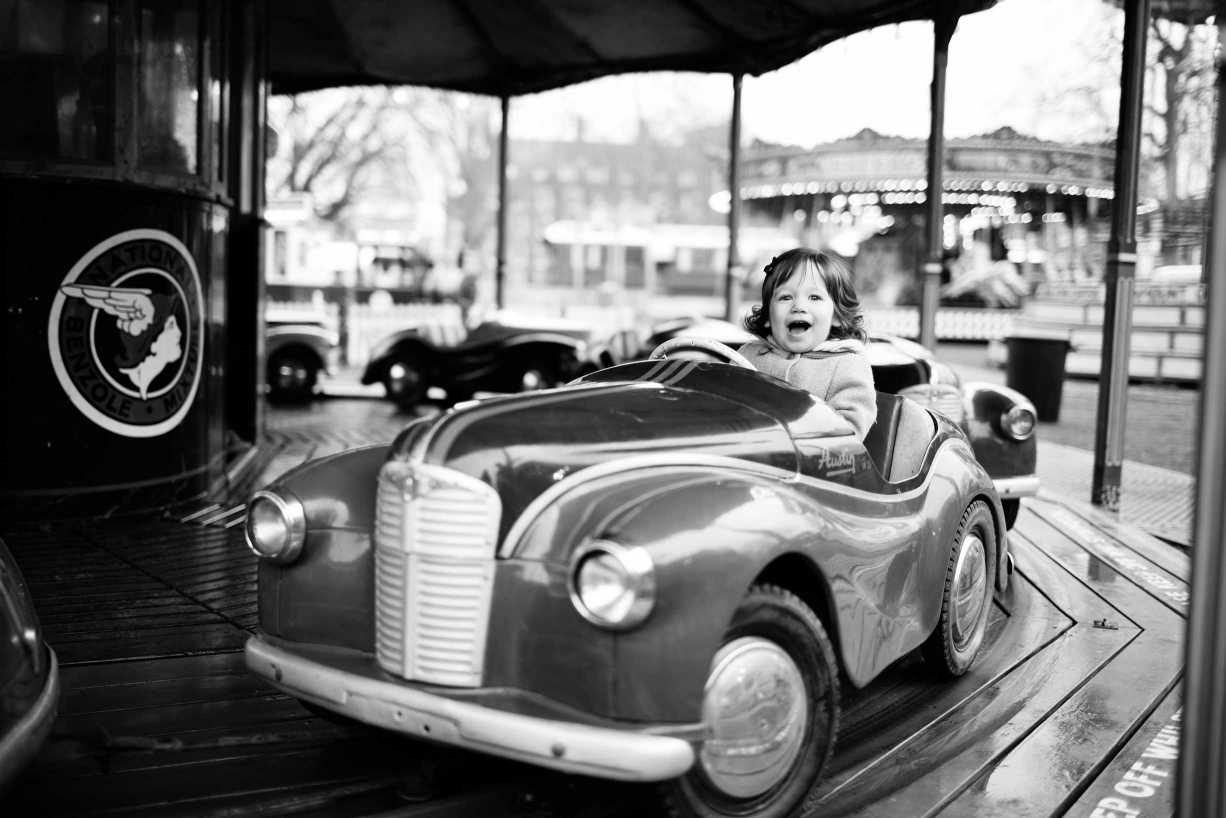 Family photography in Kensington: this little girl drives herself round in circles during her portraits.