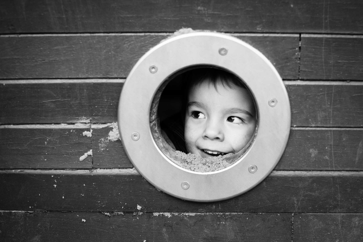 A girl looks out of a porthole at the Pirate's Ship in Hyde Park, Kensington, in this black and white family portrait.