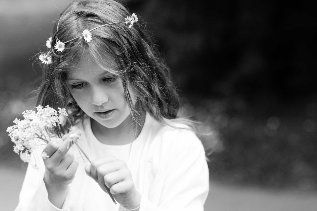A young girl in a daisy chain circlet threads more daisies during her portrait session in the wilds of Kew Gardens, on the edge of London.