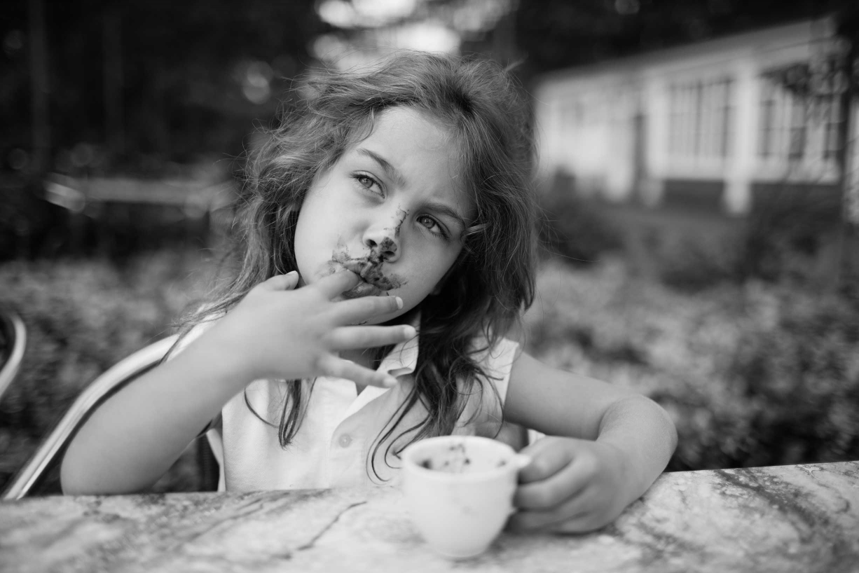 A babychino, yes please! A little girl licks froth from a cup during her family portrait session.