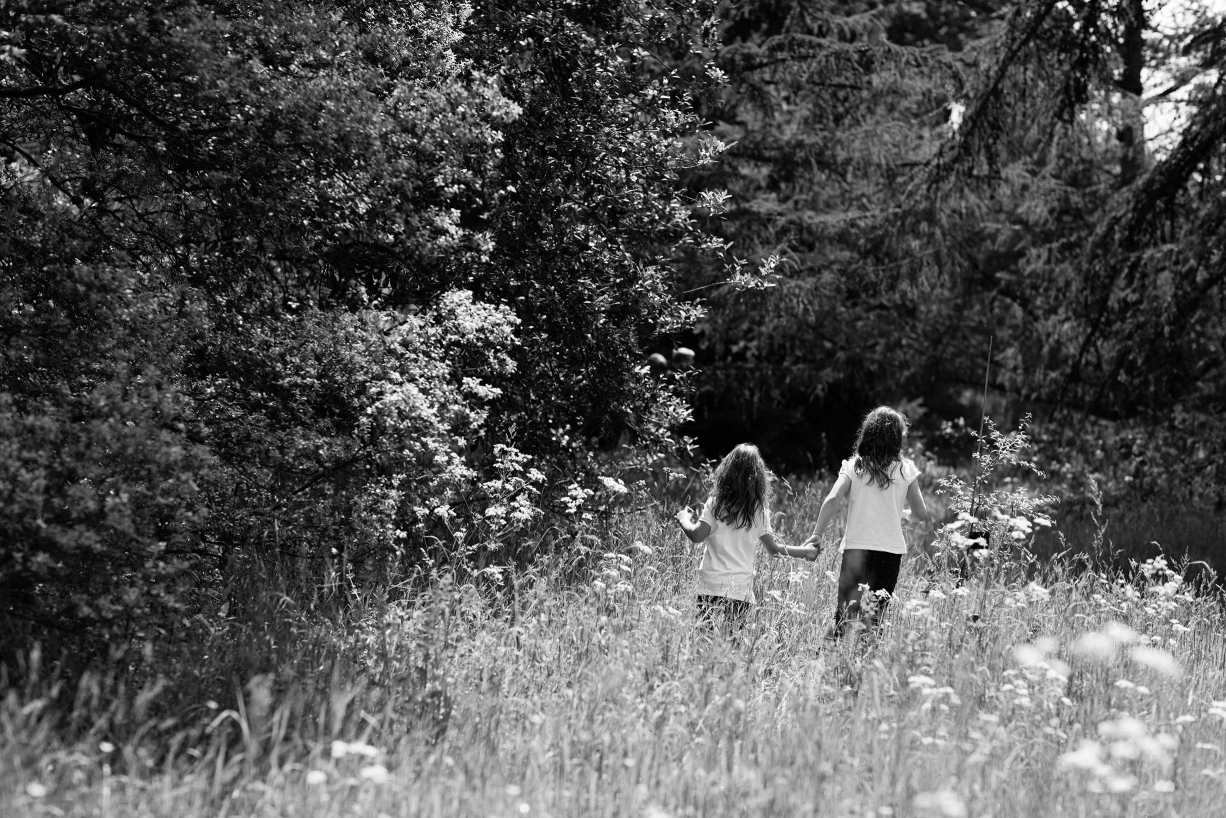 Sisters walk through the long grass during their family photograph session in Kew, west London