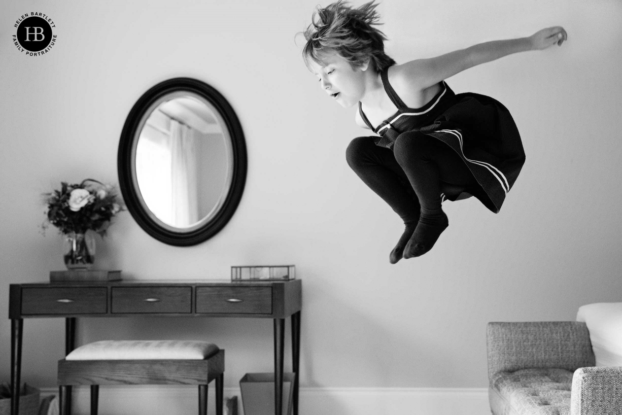A girl jumps into the air during a shoot by London photographer Helen Bartlett which involved newborn and sibling photography