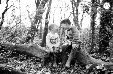 boys laugh together as they sit on a log in Streatham Woods