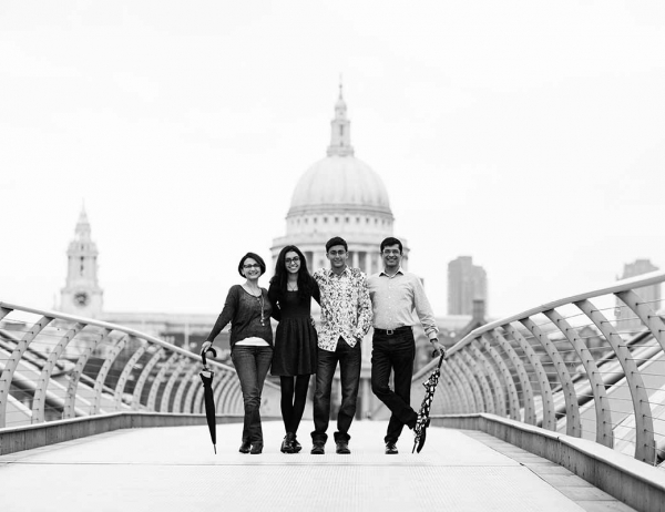 A family gathers on the Millennium Bridge in front of St Pauls Cathedral during a London family vacation photoshoot. Their London portraits were taken by city professional photographer Helen Bartlett.