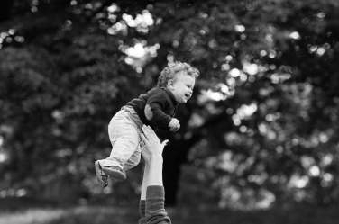 A child climbs a tree during family photography in Wimbledon, taken by Helen Bartlett.