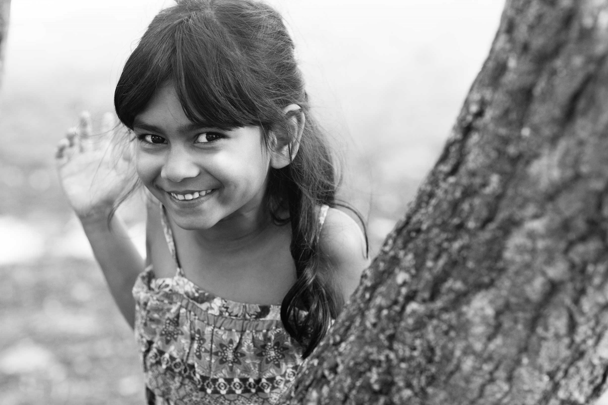 A smiling portrait of a little girl is given a dramatic emphasis with the diagonal line of this tree trunk.