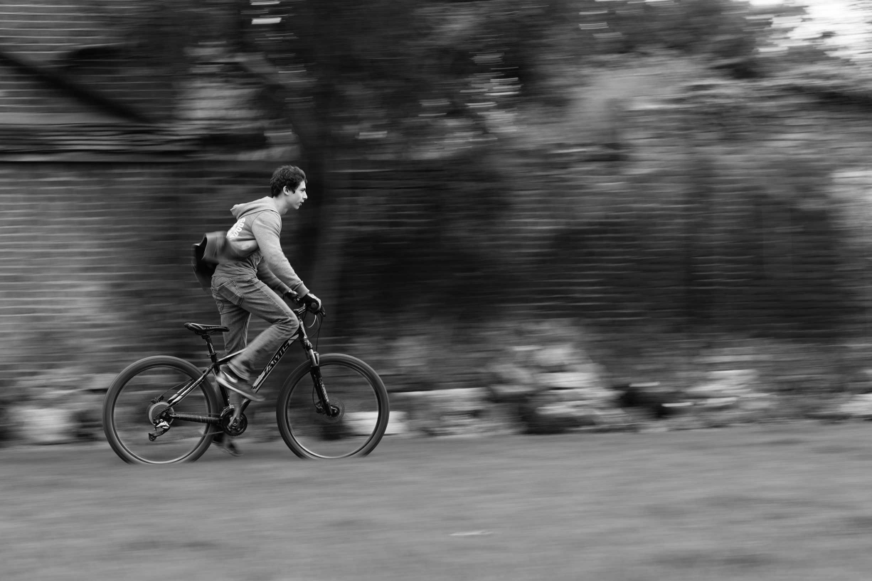 A speeding child on a bike is captured by Helen Bartlett as part of her natural style family photos. She works in an observational or photojournalistic way.